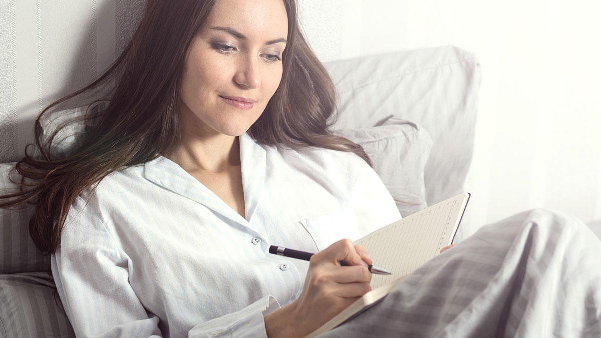 девушка пишет в блокнот в кровати