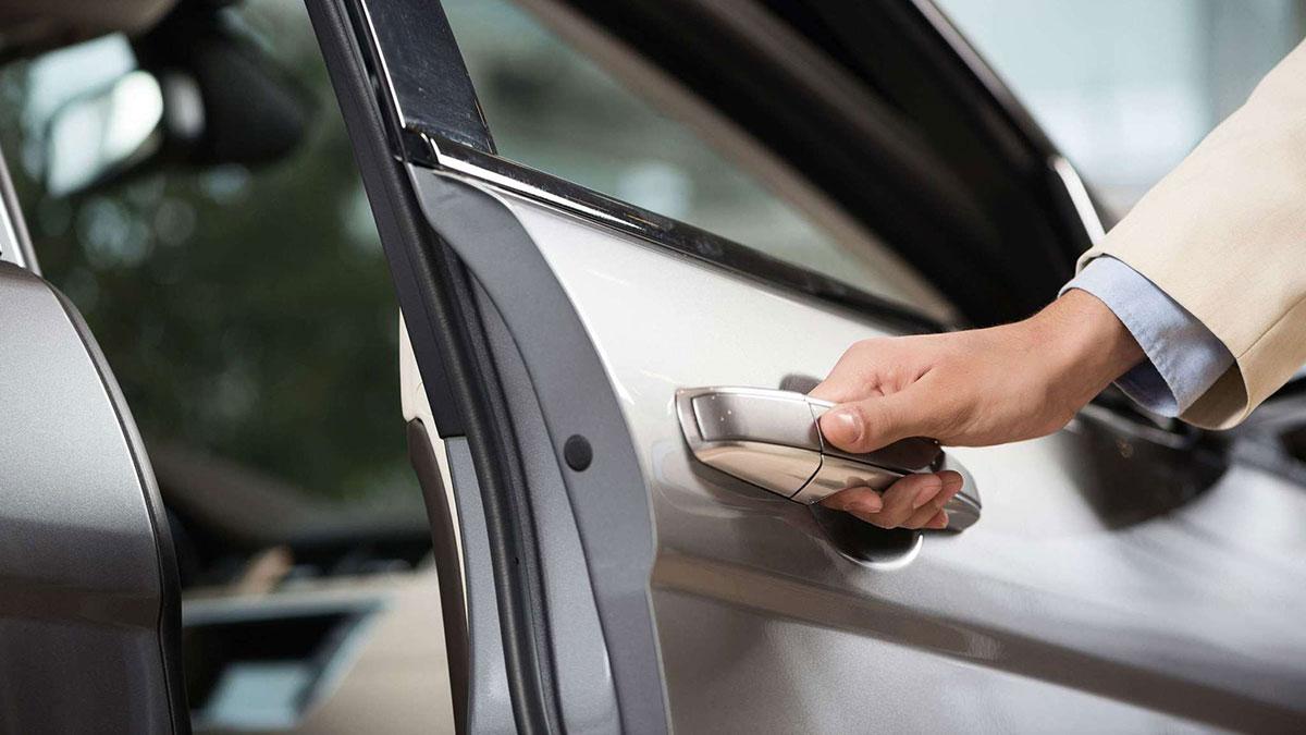 человек закрывает дверь автомобиля машина