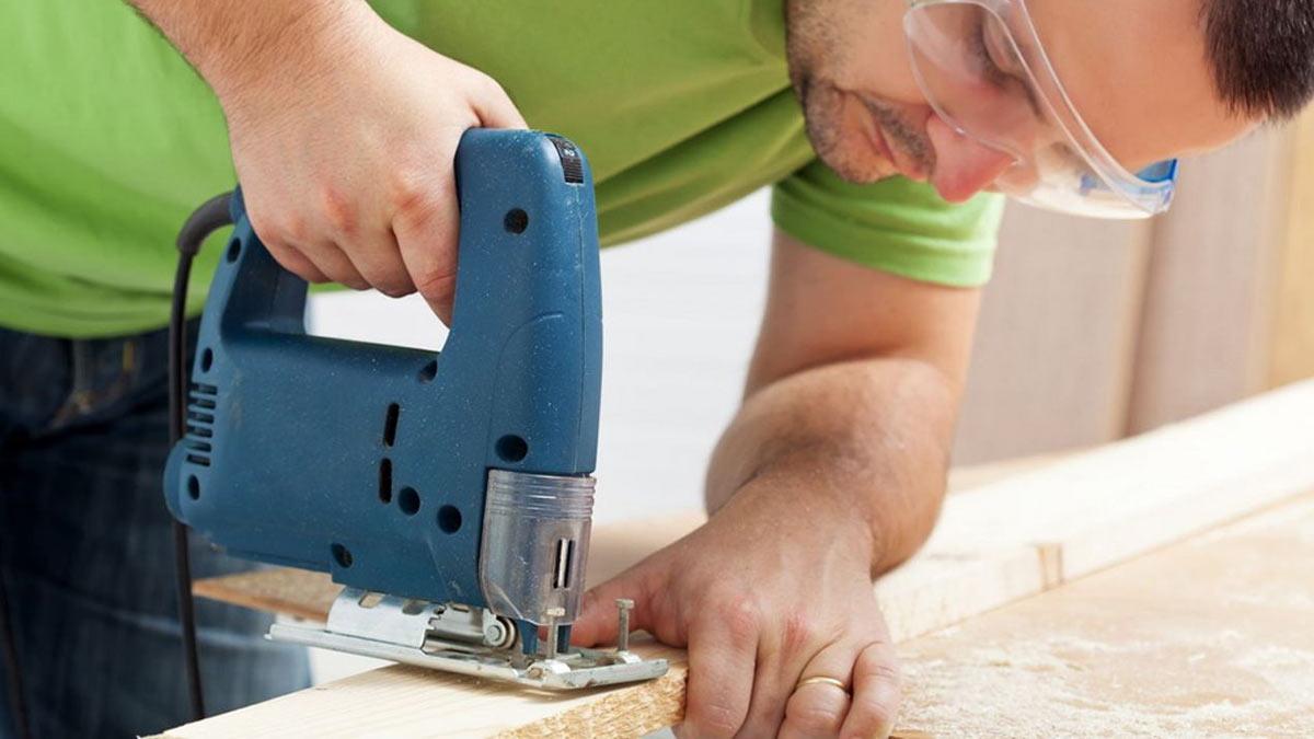 мужчина работает электролобзиком