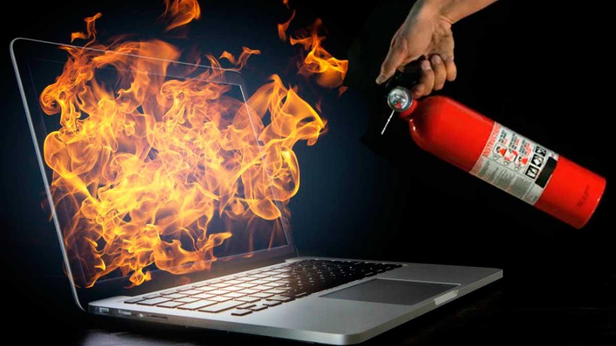 горит ноутбук рука с огнетушителем