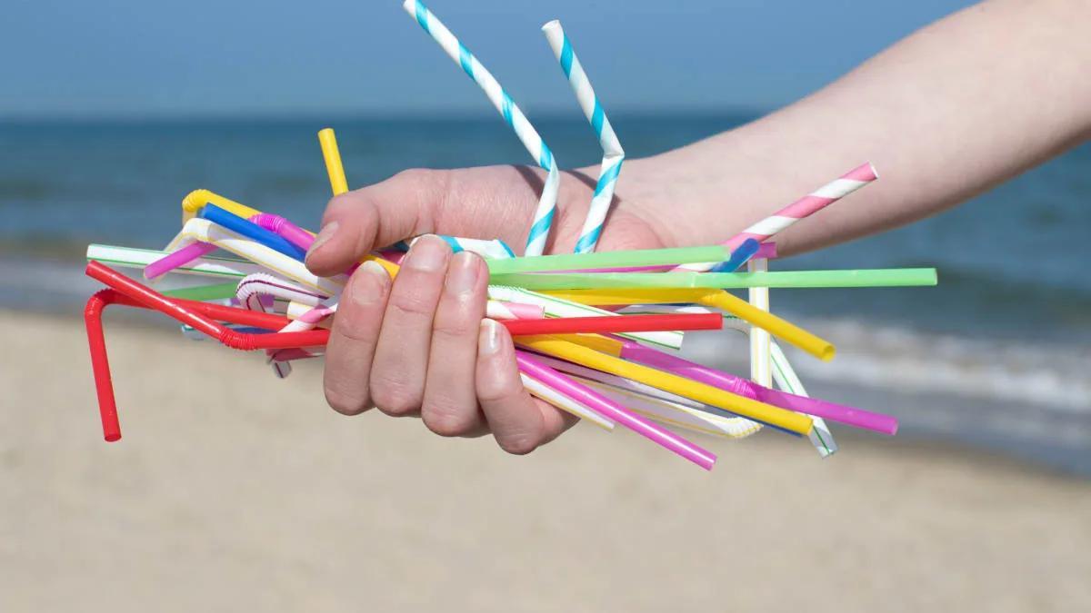 пластиковые трубочки в руке