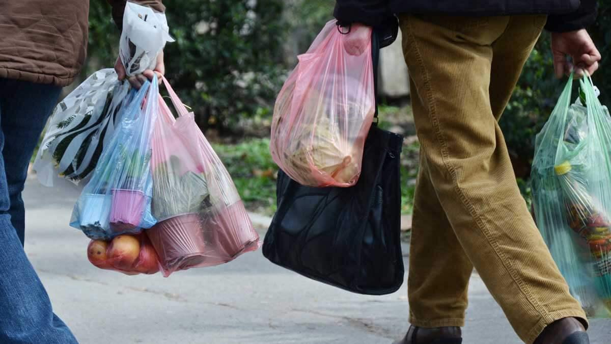 люди идут по улице продукты пластиковые пакет