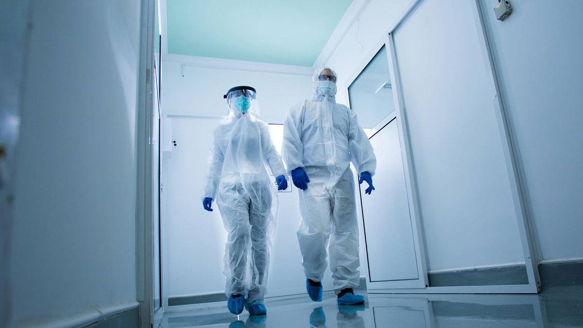 люди в защитных костюмах идут по лаборатории