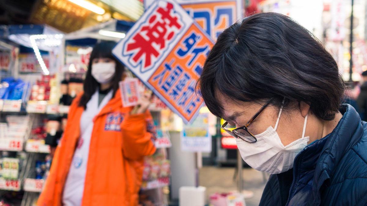 мужчина склонил голову люди маски Япония