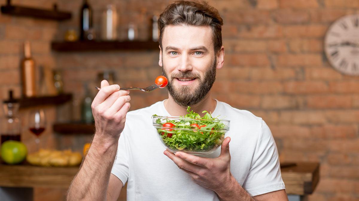 мужчина среднего возраста ест салат