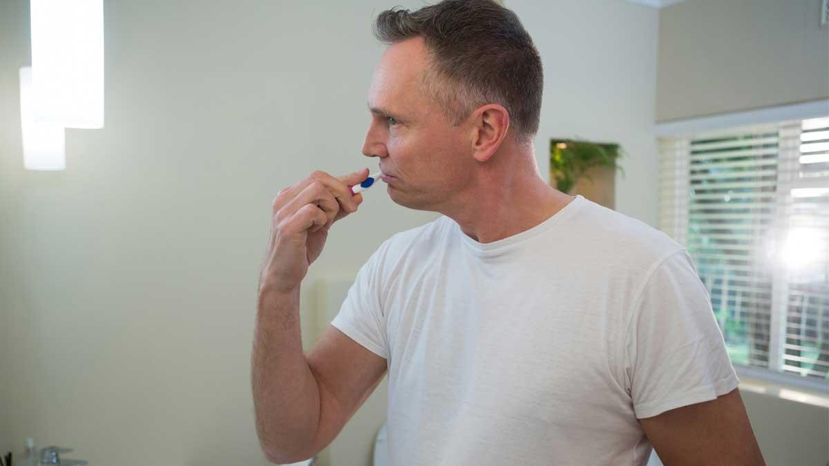мужчина в ванной чистит зубы
