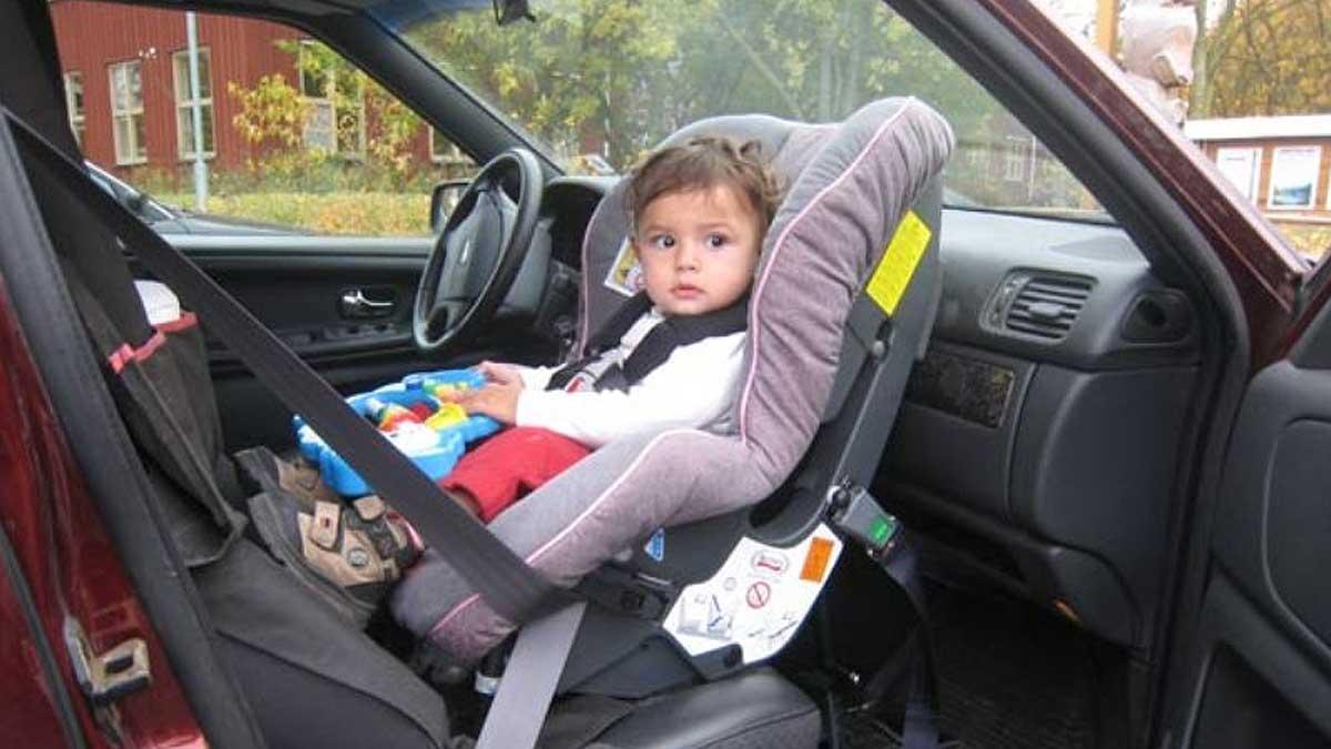 ребенок в детском кресле на переднем сидении