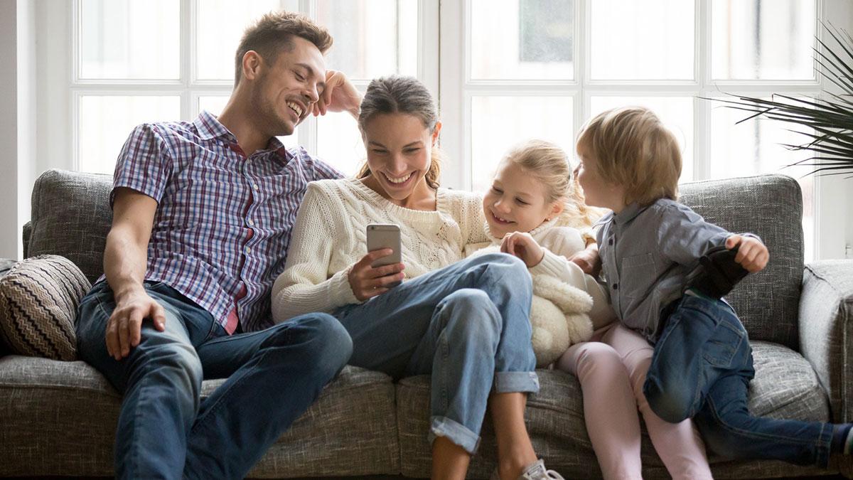 счастливая семья с детьми смотрит на экран телефона