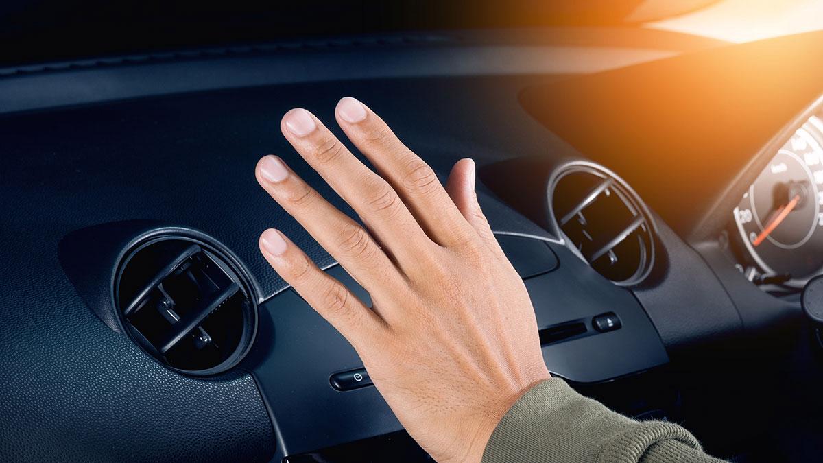 Человек проверяет рукой работу кондиционера печки в автомобиле