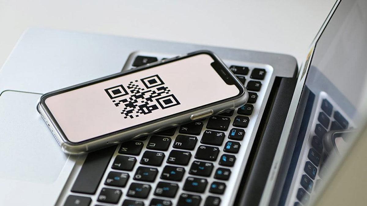 телефон с qr код лежит на ноутбуке