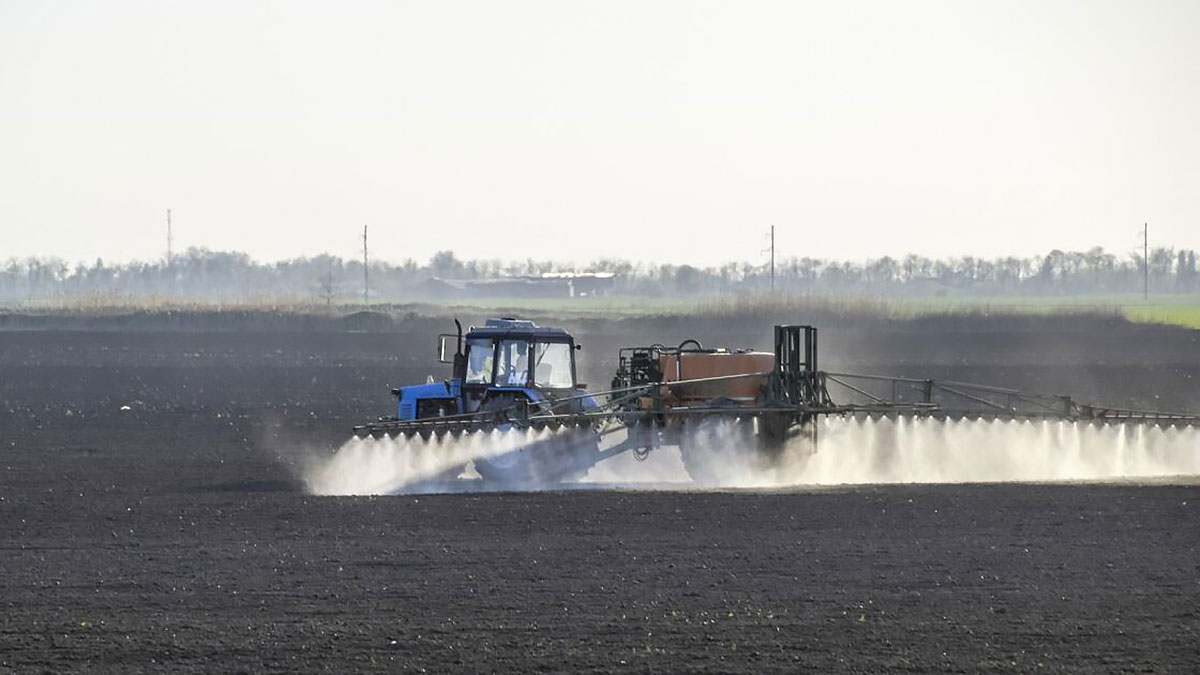 трактор поливает высохшее поле