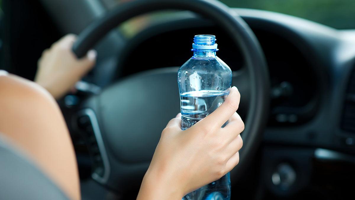 девушка пьет воду за рулем жара в машине