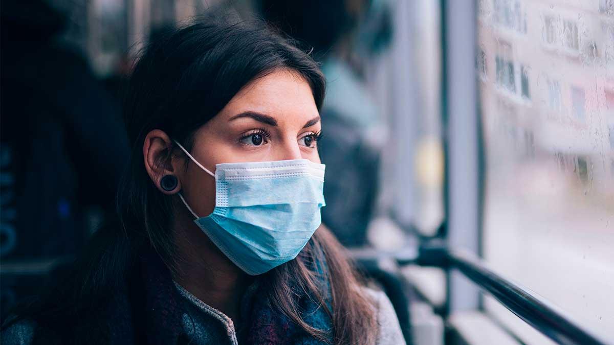 женщина в маске смотрит в окно вдаль