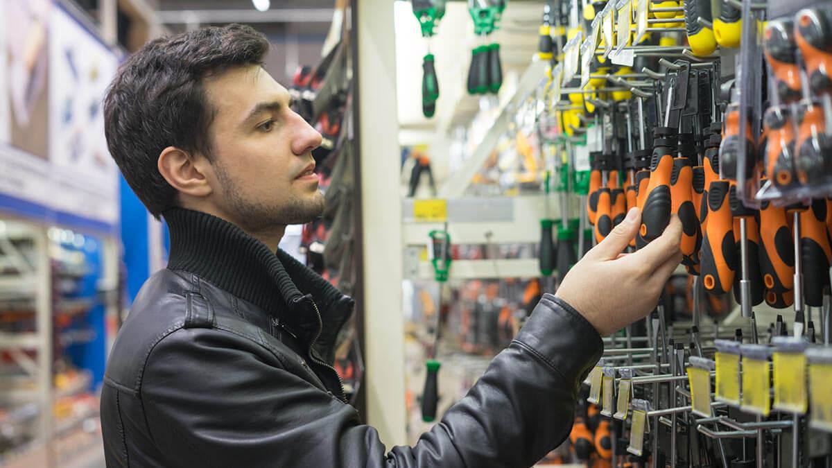 Человек выбирает отвертки в строительном магазине