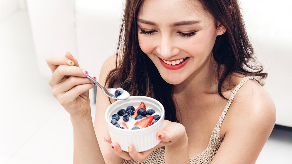 девушка ест йогурт с ягодами