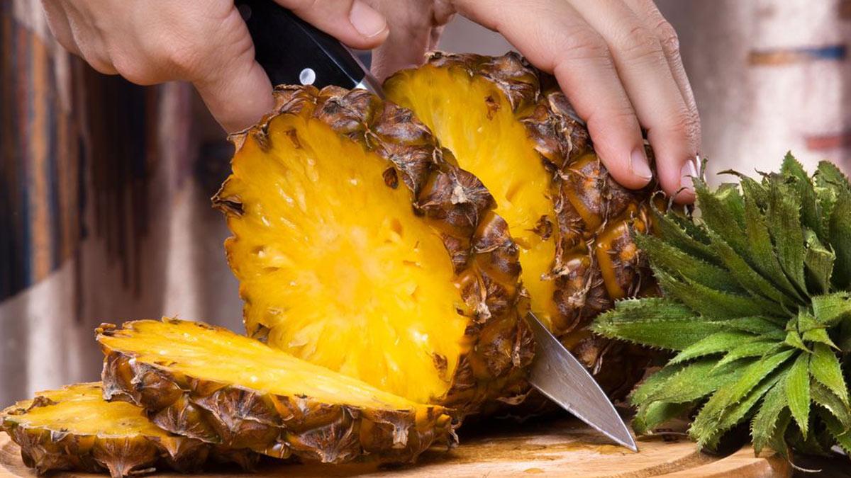 человек нарезает ананас