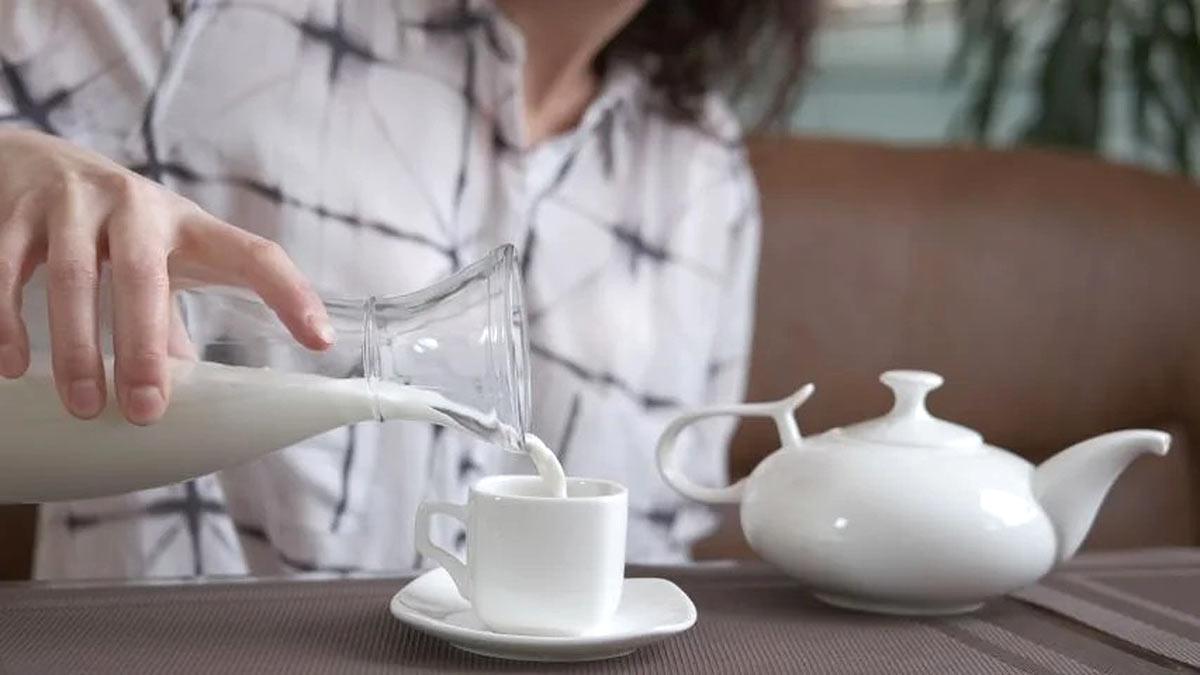 женщина наливает молоко в чашку