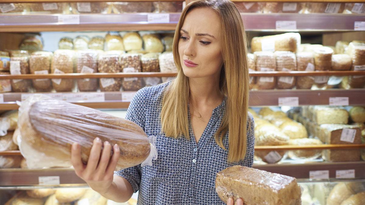 женщина выбирает хлеб в магазине