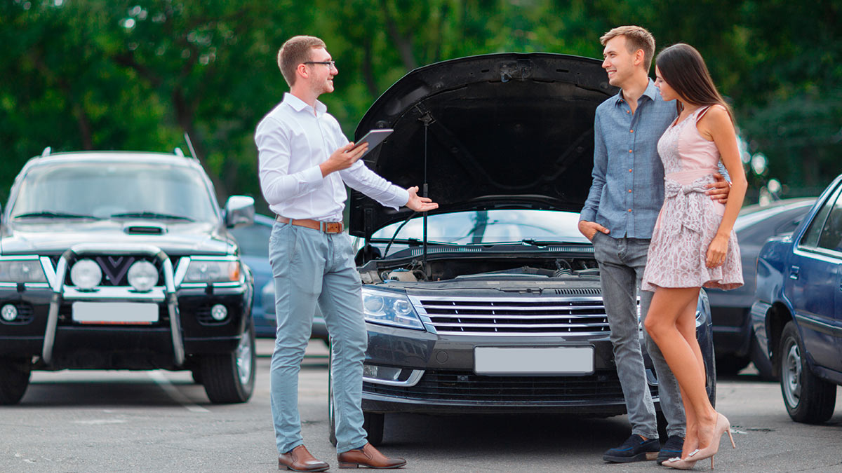 мужчина и женщина покупают автомобиль