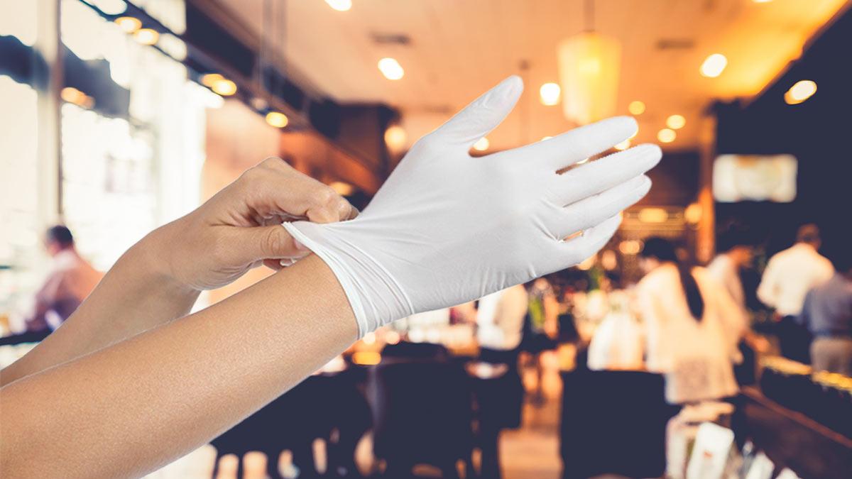 сотрудник ресторана надевает перчатки