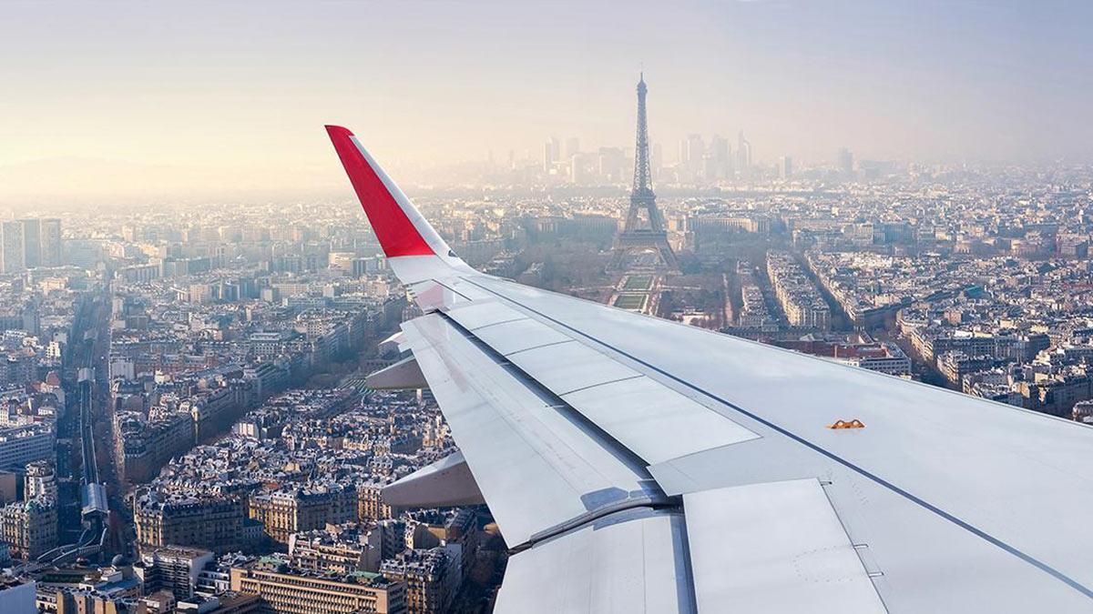 самолет летит над Парижем