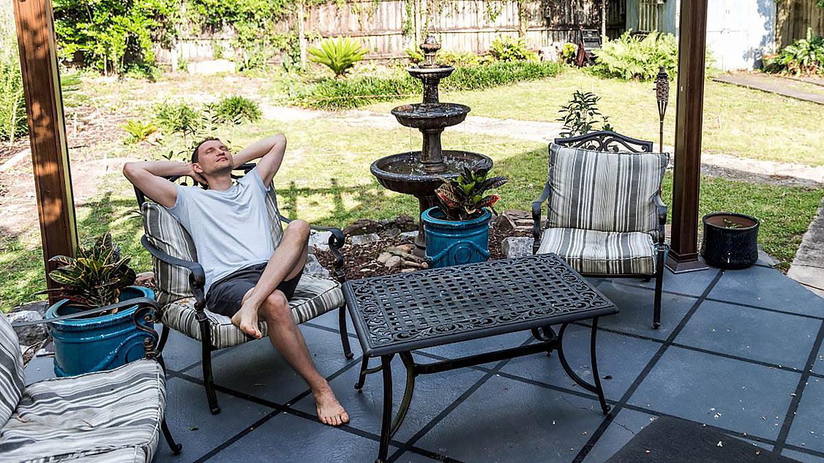 Мужчина сидит на веранде