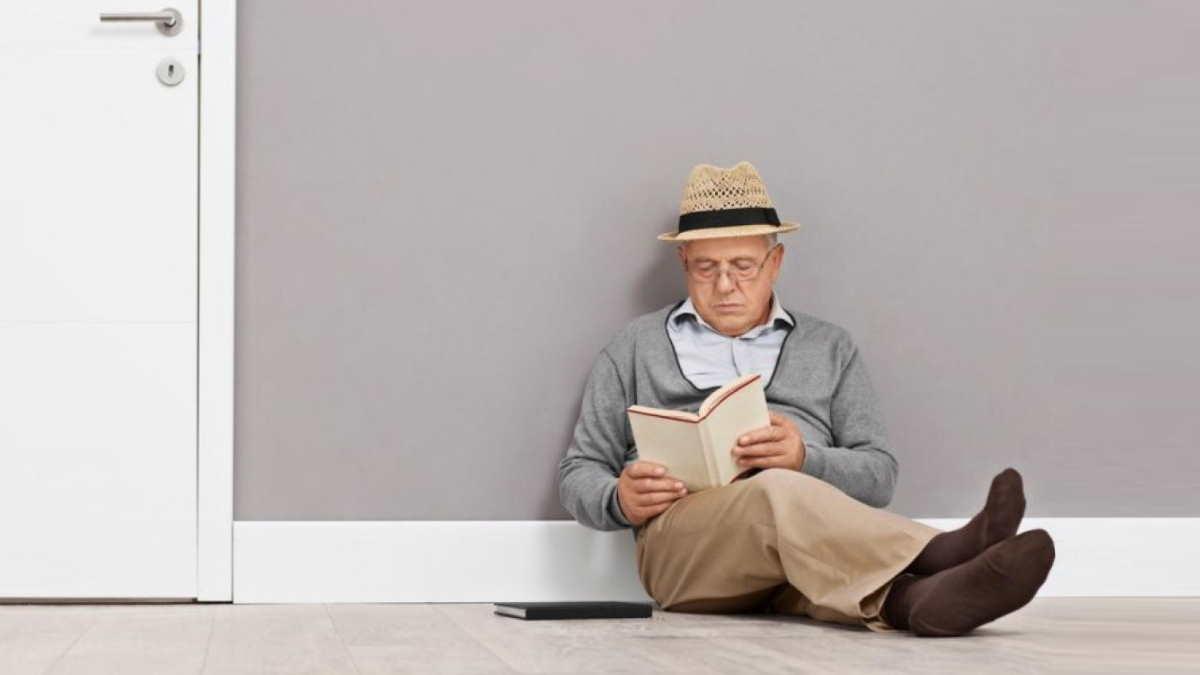 пожилой человек сидит на полу