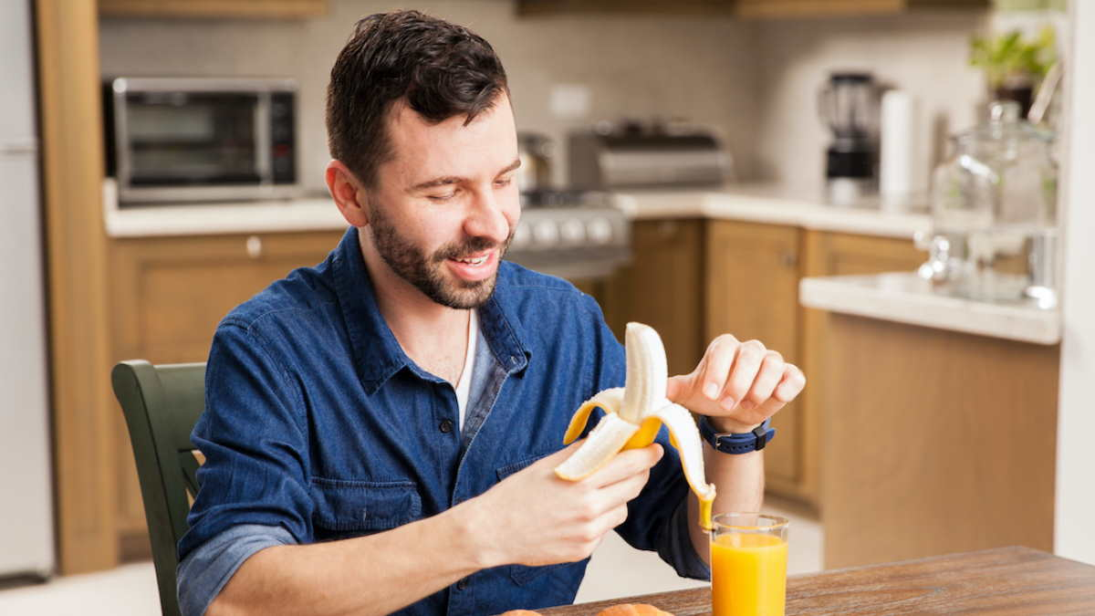мужчина ест банан