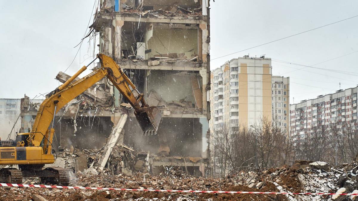 кран ломает дом здание