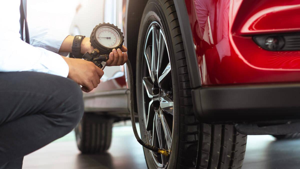 мужчина проверяет давление шин