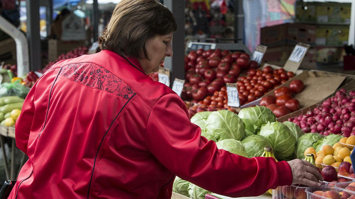 Женщина выбирает овощи на рынке