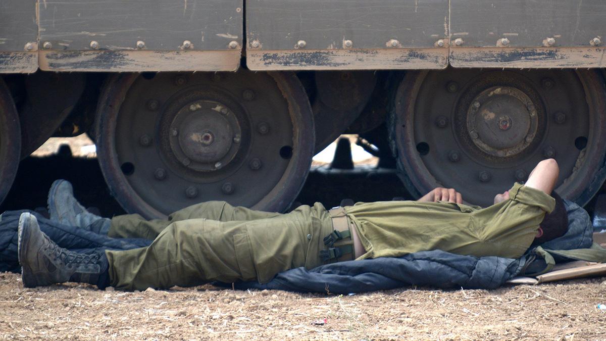 солдат спит возле танка