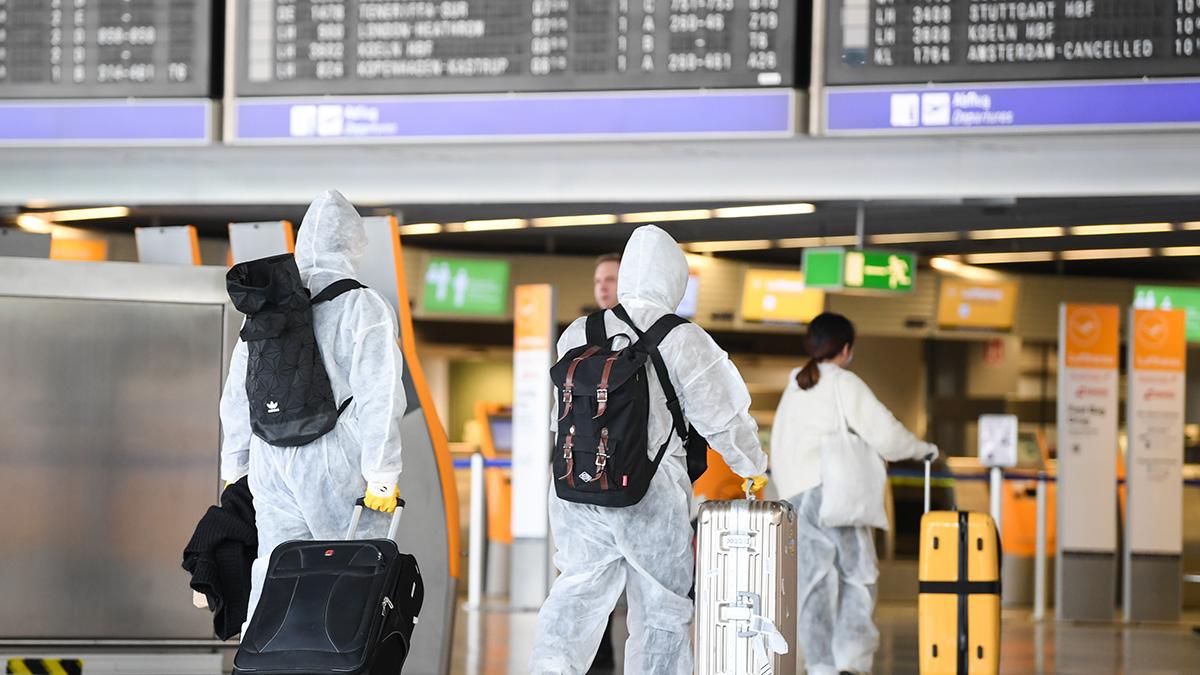Туристы в защитных костюмах в аэропорту