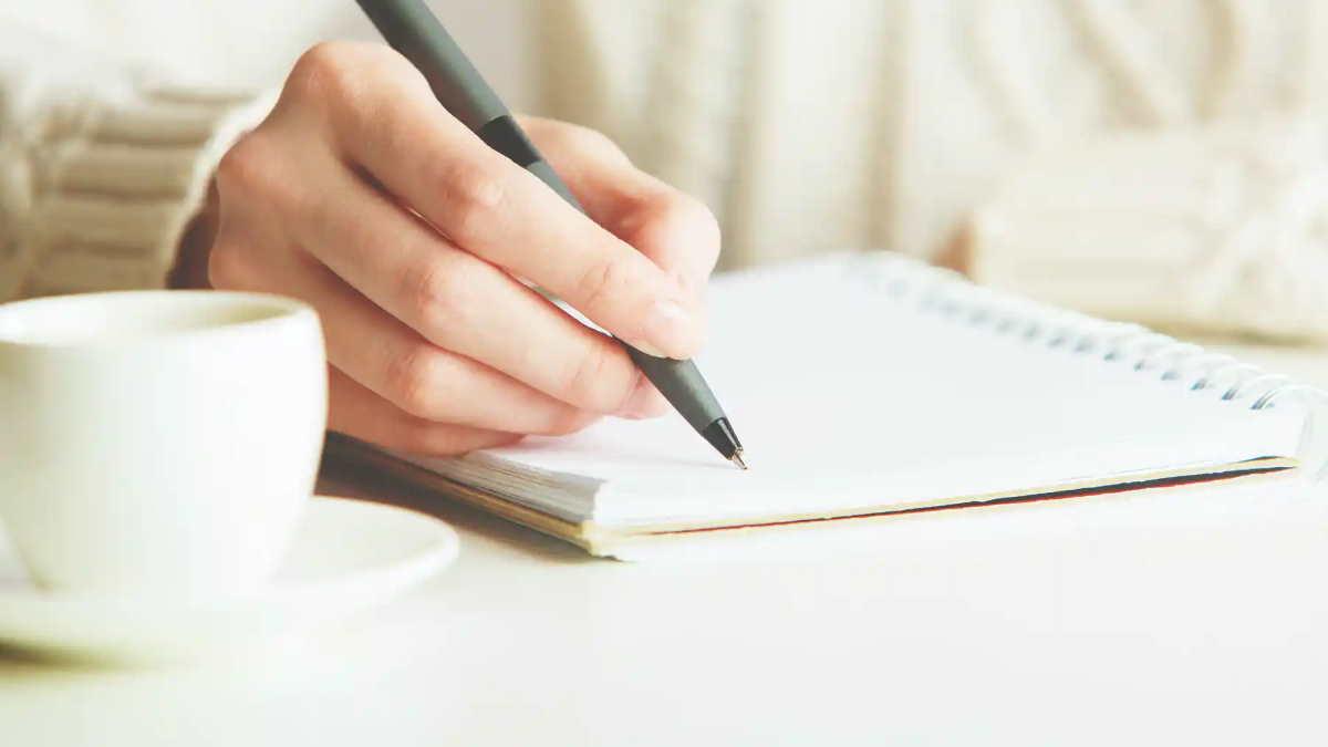 девушка пишет в блокноте