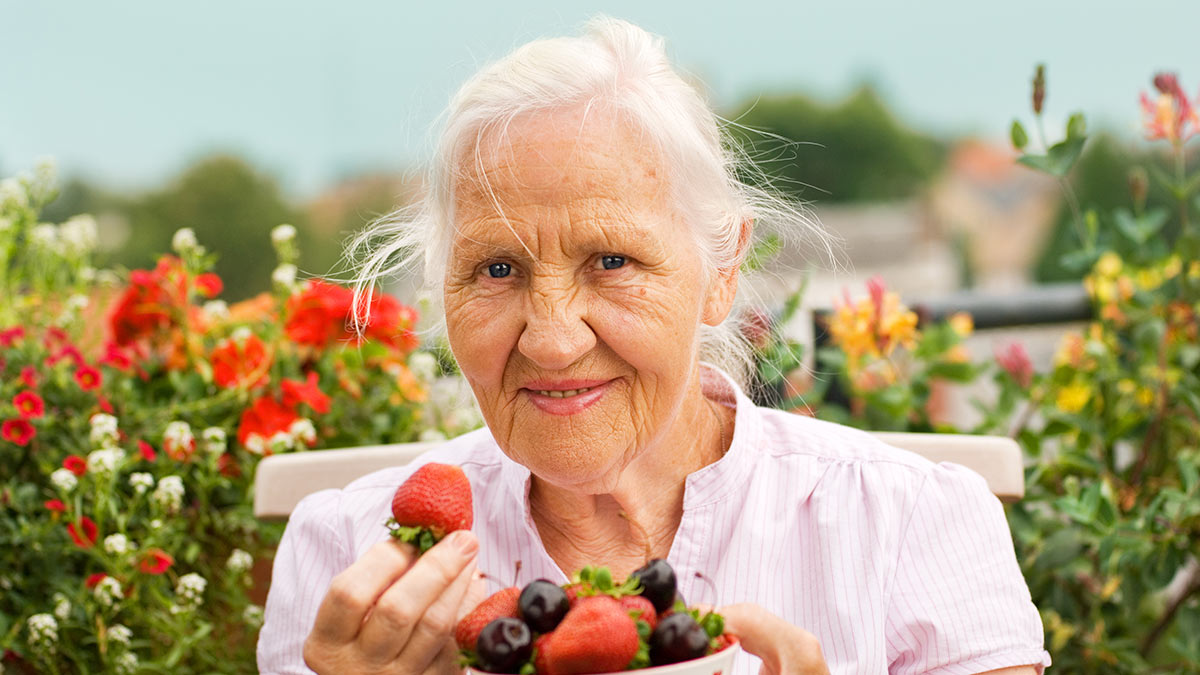 пожилая женщина держит ягоды